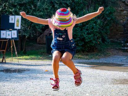 Una niña salta en el parque.