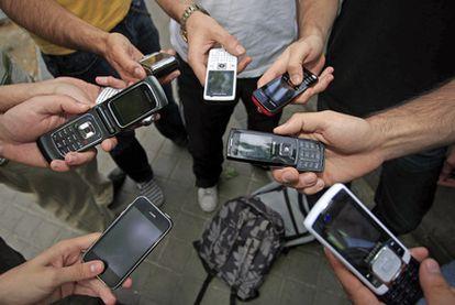 Manos de jóvenes con teléfonos móviles