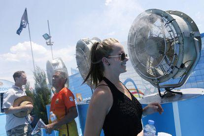 Los visitantes de un torneo deportivo se refrescan frente a algunos fanáticos.