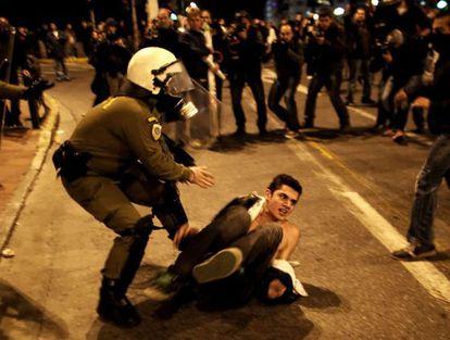 Un agente intenta reducir a un manifestante en uno de los actos de protesta celebrados en Atenas.