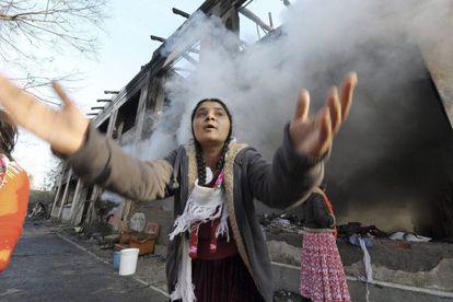 Una mujer junto a los restos de un edificio en el campo de rumanos en Turín, Italia, que fue atacado.