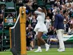 A referee helps Serena Williams of the US off the court after retiring from the women's singles first round match against Aliaksandra Sasnovich of Belarus on day two of the Wimbledon Tennis Championships in London, Tuesday June 29, 2021. (AP Photo/Kirsty Wigglesworth)
