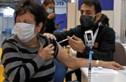Un sanitario inyecta la vacuna a una mujer en Maccabi (Israel).