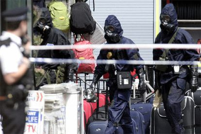 Policías británicos equipados con trajes contra agentes químicos se despliegan en la estación de metro de Warren Street.