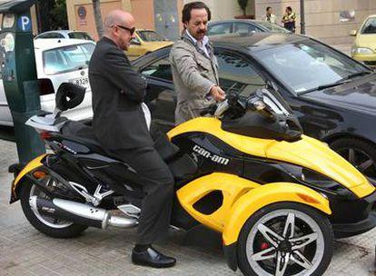 Álvaro Pérez (derecha) enseña su moto a un amigo frente a la sede del PP de Valencia.