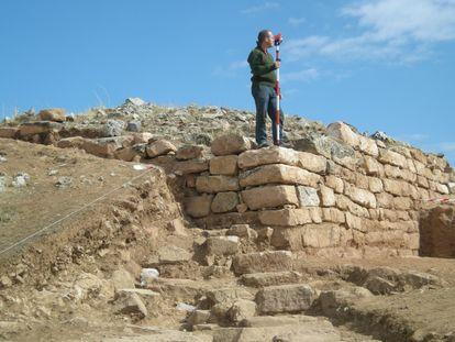Un arqueólogo sobre los restos de una de las dos torres halladas en el yacimiento de Los Rodiles (Guadalajara).