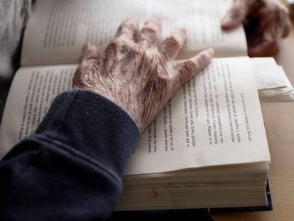 Un anciano lee un libro.
