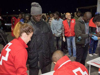 Trabajadores de la Cruz Roja reciben en el puerto de Motril (Granada) a un grupo de migrantes.