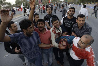 Manifestantes antigubernamentales trasladan a un compañero herido en las protestas de ayer en Manama.