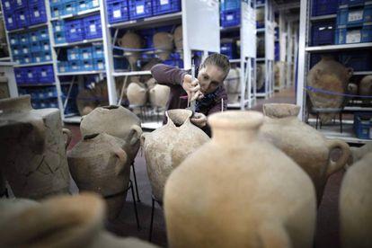 Una estudiante inspecciona unas vasijas en el Depósito de los Tesoros Nacionales.