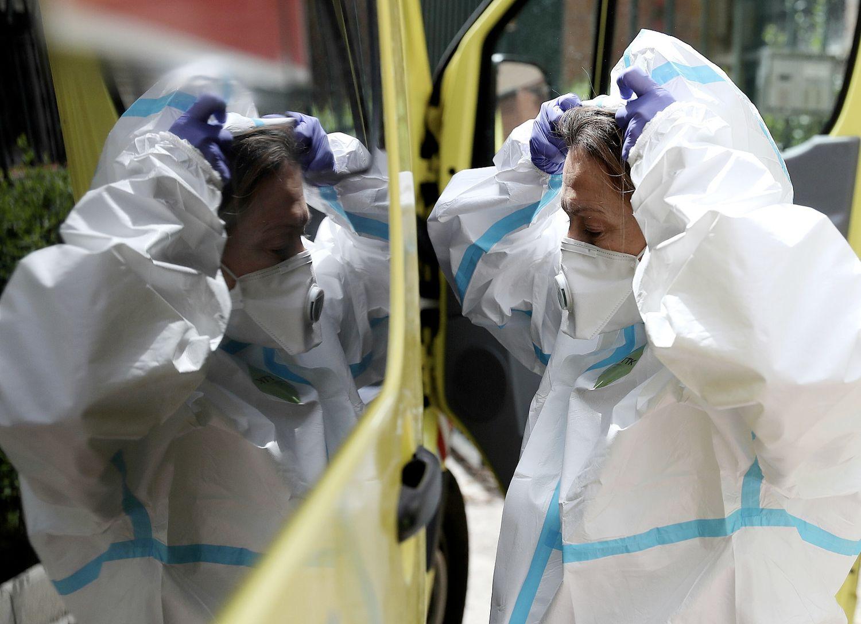 La médica se coloca el traje con el cristal de la ambulancia como ayuda, momentos antes de entrar en un domicilio, en Madrid.