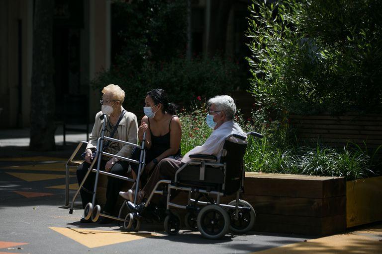 Dos ancianos junto a una joven toman el aire en el barrio de Sant Antoni de Barcelona.
