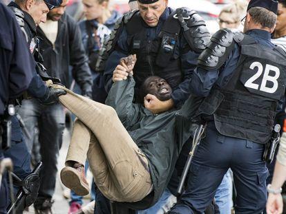 Un migrante se resiste a ser evacuado por la policía durante el desmantelamiento de un campamento temporal de inmigrantes, en la avenida Flandre en el norte de París (Francia).