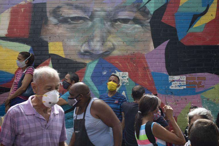 Peatones caminan frente a un mural que retrata al expresidente Hugo Chávez en Caracas, el pasado 2 de julio.