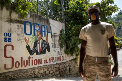 A Haitian policeman near a mural of the assassinated President Jovenel Moïse.