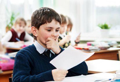 Un niño mira con detenimiento una hoja.