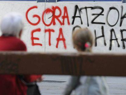 Dos personas sentadas ante una de las pintadas en favor de ETA, en Vitoria.
