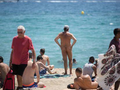 Un nudista en la playa de la Mar Bella rodeado de personas en traje de baño.