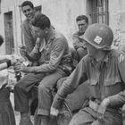 Una mujer sirve vino a soldados aliados durante la liberación de Francia.