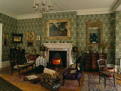 Salón de estilo eduardiano con papel tapiz verde de William Morris.