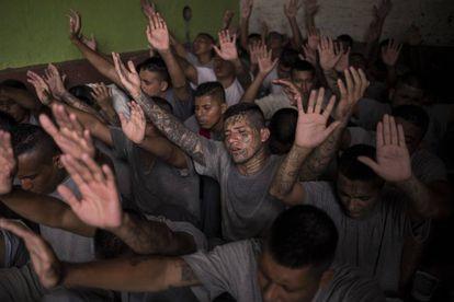 Antiguos pandilleros, recluidos en la cárcel de Gotera, levantan las manos durante el servicio religioso.