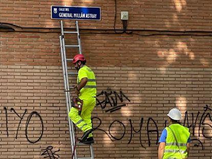 Dos operarios colocan el nuevo rótulo de la calle General Millán Astray en el callejero de Madrid.