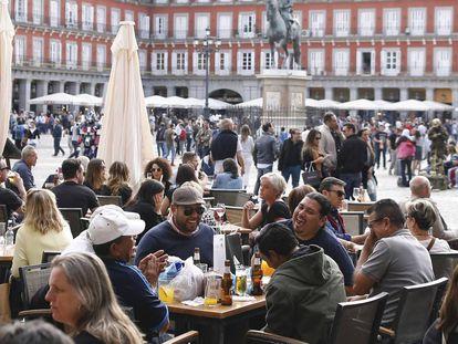 Las terrazas de los bares de la plaza Mayor de Madrid llenos de gente, consumiendo cerveza y disfrutando del buen tiempo, que atrae a visitantes y turistas.