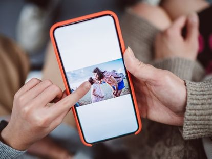 Un teléfono muestra la imagen de una madre con su hija.