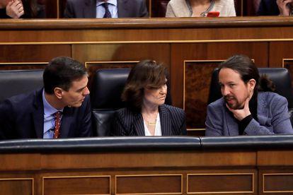 El presidente del Gobierno, Pedro Sánchez, conversa con la vicepresidenta primera, Carmen Calvo, y con el vicepresidente de Derechos Sociales y Agenda 2030, Pablo Iglesias, durante el pleno celebrado este jueves en el Congreso.