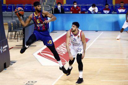 Barça's American center Brandon Davies saves a ball with Anadolu Efes' Vasilije Micic during the EuroLiga regular phase match between Barça and Anadolu Efes.