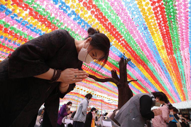 Creyentes protegidos con mascarillas conmemoran en un templo de Seúl el cumpleaños de Buda.