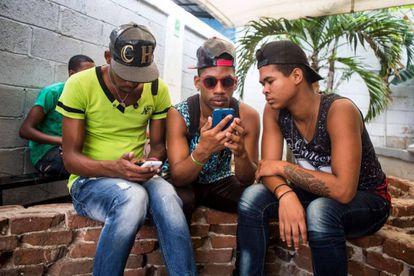 Tres jovenes en La Habana conectados al Wi-Fi con sus móviles en 2016.