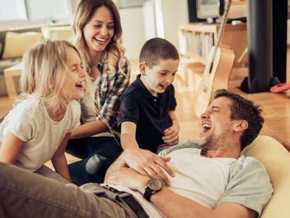 Niños y padres se ríen en el sillón.