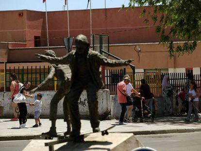 Un colegio en la Avenida Juan Carlos I de Parla, junto a la estatua de unos niños en monopatín.