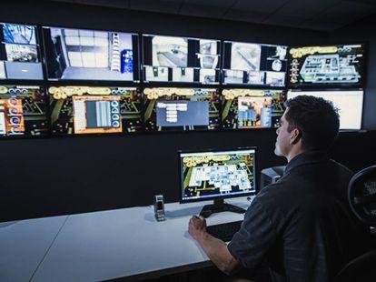 Un vigilante observa los monitores en una sala de seguridad.