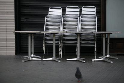 Sillas apiladas en el bar Zúrich, de Barcelona, cerrado este viernes.