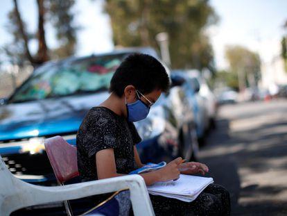 Un estudiante hace los deberes en la calle mientras su madre trabaja en un estacionamiento público, en Ciudad de México.