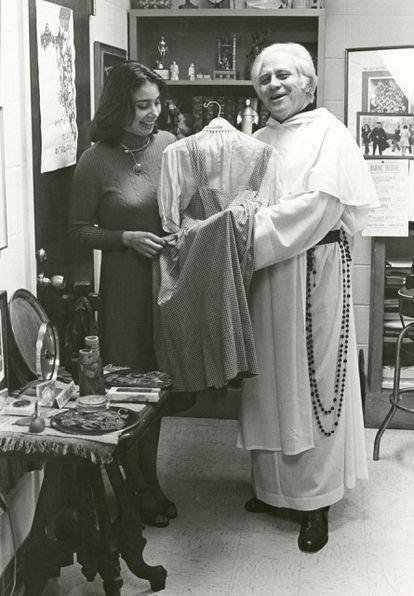 Una fotografía divulgada por la Universidad Católica de América donde aparece el padre Gilbert Hartke y la estudiante Carol Pearson mientras sostienen el vestido de Dorothy en 'El mago de Oz' de 1939.