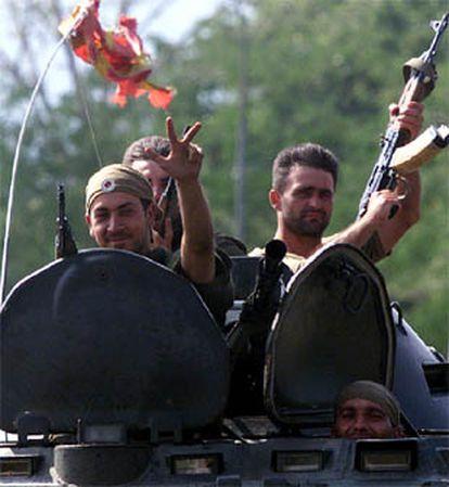 Soldaos macedonios saludan haciendo un gesto tradicional ortodoxo mientras saludan a las afueras de Skopje