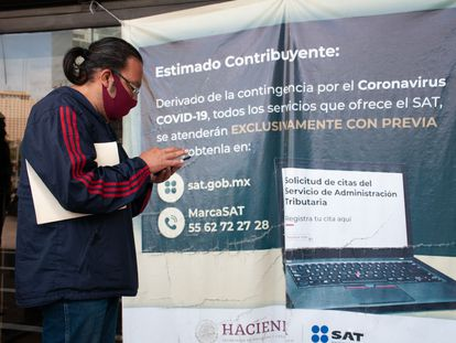 Un hombre revisa su teléfono móvil frente a las oficinas del Servicio de Administración Tributaria (SAT).