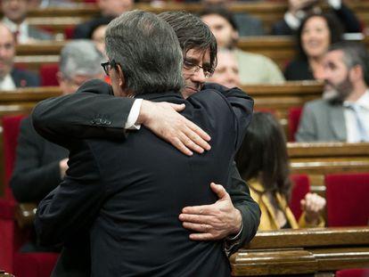 El presidente catalán en funciones, Artur Mas (de espaldas), saluda a Carles Puigdemont, poco antes de comenzar el pleno del Parlament en el que se debate la investidura de Puigdemont como nuevo presidente de la Generalitat, tras el pacto alcanzado ayer in extremis entre Junts pel Sí y la CUP.