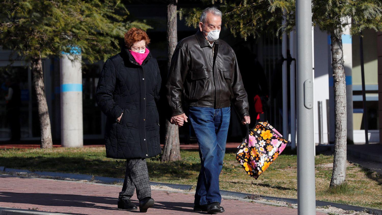 Una pareja con mascarillas vista en el exterior del Hospital de Torrejón de Ardoz. Chema Moya (EFE)