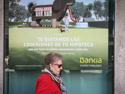Una mujer pasa ante cartel que publicita hipotecas en una sucursal bancaria.