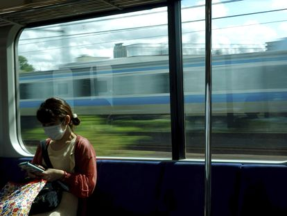 Una mujer mirando su teléfono en un tren de Tokio, este sábado.