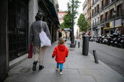 Un niño de dos años acompaña a su madre a hacer la compra, en Madrid.