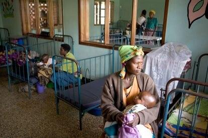 Una madre acuna en sus brazos a su hijo, enfermo de malaria, en el hospital de Ibanda, en Uganda.