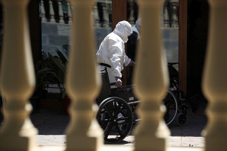"""Un trabajador introduce una silla de ruedas en la residencia de Mayores """"San Marcos"""" en San Martin de la Vega, en Madrid, este jueves."""