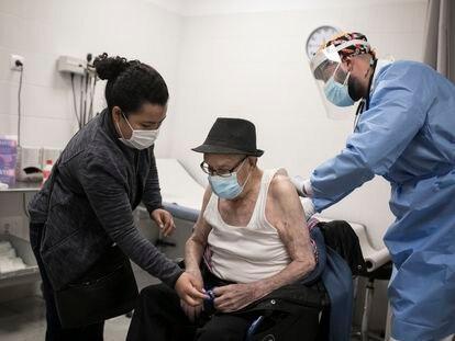 Un paciente, acompañado de su cuidadora, es atendido por un médico en un centro de salud.