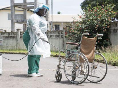 Una enfermera desinfecta una silla de ruedas en Ghana.