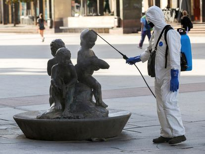 Un operario del servicio de limpieza desinfecta una fuente de la plaza del Pilar de Zaragoza.